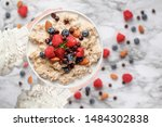 Healthy oatmeal served with berries, chocolate chips, almonds and honey. Bowl held in a womans hands over a marble table background. Shot from top view. - stock photo