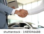 Young salesman shaking hands with client in modern car dealership, closeup - stock photo