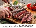 hands cut grilled tomahawk meat ... | Shutterstock . vector #1485084605