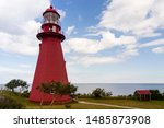 Horizontal view of beautiful octogonal 1906 red wood shingled lighthouse in summer, La Martre, Quebec, Canada