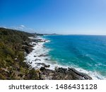 Bright sunny summer beach day with vivid blue ocean in the background and cliffs in the foreground at Point Arkwright, Sunshine Coast, Queensland, Australia