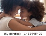 Small photo of Close up head shot side view calm happy mixed race mother cuddling little cute daughter, touching foreheads. Tender moment family support, forgive and understanding. Adopted kid hugging foster mom.