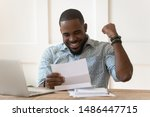 Small photo of Happy euphoric young african american guy received paper report, university admission letter, celebrating important goal achievement, banking loan approval, full credit repayment, lottery win notice.