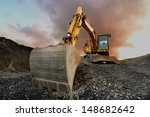 Small photo of Image of a wheeled excavator on a quarry tip