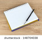 notebook and pen on wooden table | Shutterstock . vector #148704038