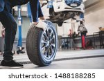 Small photo of Male mechanic hold and rolling tire at repairing service garage background. Technician man replacing winter and summer tyre for safety road trip. Transportation and automotive maintenance concept