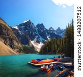 Small photo of Canoes on a jetty at Moraine lake in Banff National Park, Alberta, Canada, with snow-covered peaks of canadian Rocky Mountains in the background.