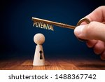 Small photo of Coach has a key to unlock potential - motivation concept. Coach (manager, mentor, HR specialist) unlock leader potential and talent represented by wooden figurine and hand with key.