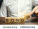 Small photo of Businessman puts wooden blocks with the word Bonds. A bond is a security that indicates that the investor has provided a loan to the issuer. Equivalent loan. Unsecured and secured bonds.