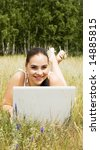 happy woman with laptop on the green grass - stock photo