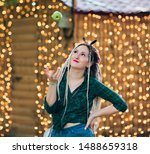 Small photo of Inordinate young woman with dreadlocks hairstyle and fashionable summer clothes throws an apple against the background of garlands