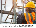 [safety body construction] Working at height equipment. Fall arrestor device for worker with hooks for safety body harness on selective focus. Worker as in construction background. - stock photo