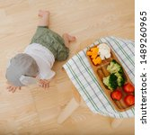 Small photo of Active restless infant child with rabbit ears hat is hastily crawling away from his dinner. Shot from above.