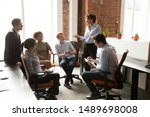 Small photo of Middle aged female team leader or boss hold casual group meeting talking with employees brainstorming in shared office, manager speak sharing ideas at informal briefing with coworkers