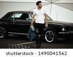 Handsome man with black old car waliking on the parking - stock photo