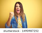 Small photo of Young beautiful woman standing over yellow isolated background angry and mad raising fist frustrated and furious while shouting with anger. Rage and aggressive concept.
