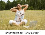 happy woman with laptop on the grass - stock photo