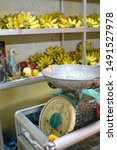Small photo of Siem Reap, Cambodia - April 11 2010 - Bright yellow bananas behind a scale on display at a covered food market in Siem Reap, Cambodia.