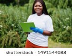Small photo of African volunteer woman with clipboard in park. Africa volunteering, charity, people and ecology concept.