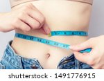 Small photo of Woman measures the girth around the waist measuring tape. Concept of diet and body weight control, close up, toned
