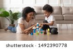 Biracial mother and small cute little son play with colorful toy blocks set building castle enjoy time together, spending weekend in living room modern home with underfloor heating system wooden floor