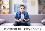 Small photo of Focused teenage boy playing video game at home, gadget addiction in awkward age