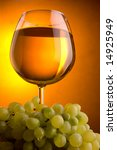 a glass of white wine and green grape - stock photo