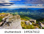 giant stones in the grass on the top of mountain meadows in a horizontal landscape - stock photo