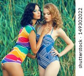 Portrait of two gorgeous young women (girlfriends) in trendy colorful swimsuits posing on the beach. Disco (70s, vintage) style. Arty make-up. Sunny summer day. Outdoor shot - stock photo