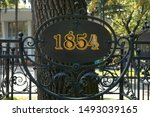 1854 year sign on metal forging fence in front of big tree. Information table placard or signboard in park or botanic garden to designate remarkable date or event