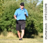 Small photo of Unemotional Older Retiree Person With Golf Club On Golf Course