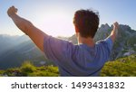 CLOSE UP LENS FLARE: Ecstatic young man standing on mountaintop, outstretching arms in victory at breathtaking summer sunset. Unknown hiker celebrating steep mountain climb and enjoying the scenery.