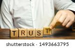 Small photo of Wooden blocks with the word Trust. Trust relationships between business partners, friends, relatives. Respect and authority. Confidence in a person. Reliable partner