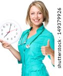 Young happy lady doctor is holding clock showing seven, isolated over white - stock photo