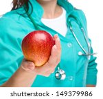 Young lady doctor is holding a red apple, isolated over white - stock photo