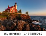 Early morning sunrise illuminates the rocks and front of Eagle Harbor Light on the Keweenaw Peninsula in Michigans Upper Peninsula. Waves from Lake Superior wash against the rocks.