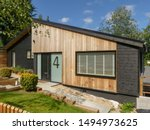 Small photo of Chorleywood, Hertfordshire, England, UK - September 3rd 2019: A refurbished 1960's bungalow clad with external western red cedar and black timber rainscreen cladding