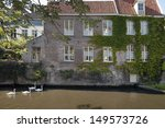 Swans swimming in the channel in Bruges, Belgium  - stock photo