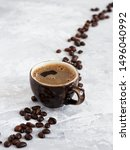 Small photo of Cup with dark espresso arranged on a gray background. Roasted coffee beans are located around a cup of coffee.
