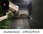 Small photo of Thief wearing black suit with balaclava and glove being caught by CCTV, surveillance camera during sneak into a house at night