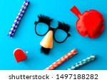 Small photo of Comical prank, April fools practical joke and goofy disguise concept farting bag, chattering teeth, chinese finger trap and novelty glasses with fake nose and eyebrows isolated on blue background