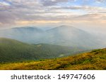 Pink morning fog in the mountains covers the top of the ridge - stock photo