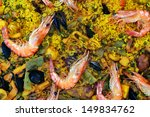 closeup of a typical paella mixta from Spain, with seafood and chicken - stock photo