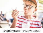 Small photo of Trendy kid drinking a milkshake at the bar. Colorful portrait of young boy holding a glass with a fresh beverage. Teen sucks a cold drink with a straw enjoying taste. Greedy, gluttonous tasty concept.