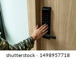 Closeup of a woman's finger entering password code on the smart digital touch screen keypad entry door lock in front of the room. Self Check-in, Modern security,Temporary codes.  - stock photo