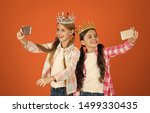 Small photo of Girls taking selfie photo smartphone camera. Spoiled children concept. Egocentric princess. Kids wear golden crowns symbol princess. Warning signs of spoiled child. Avoid raising spoiled kids.