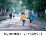 Children run in raincoats  ...