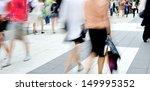 Motion blurred pedestrians on shopping street - stock photo