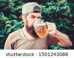 Enjoying his alcoholic beer. Bearded man drinking alcoholic drink in summer. Hipster with alcoholic beverage on nature. He is a beer drinker not an alcoholic.