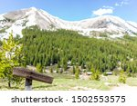 Independence Pass mining townsite and wooden signpost on trail for closed for revegetation in White River National Forest in Colorado with snow mountain peaks